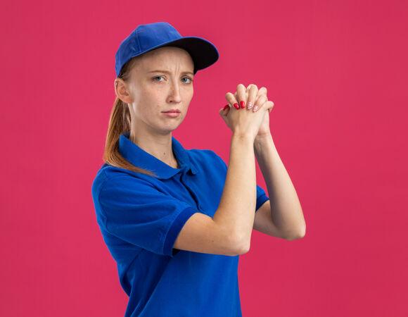 身穿蓝色制服 头戴鸭舌帽的年轻送货员 表情严肃自信 手牵手 站在粉色的墙上 做出团队合作的姿态