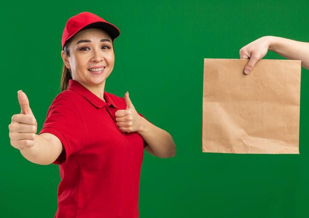 年轻的送货员身穿红色制服 头戴鸭舌帽 微笑着竖起大拇指 站在绿色的墙边收包裹