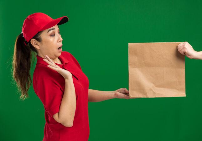 年轻的送货女孩穿着红色制服 戴着帽子 拒绝接受纸包裹 看着它惊讶地站在绿色的墙上