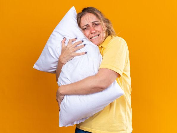 穿着黄色衬衫的不健康的女人感觉身体不适患流感 站在橘黄色的墙上抱着发烧的抱枕