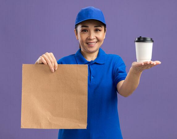 身着蓝色制服 头戴鸭舌帽 手持纸袋 脸上带着微笑 站在紫色的墙上 送纸杯的快乐年轻女快递员