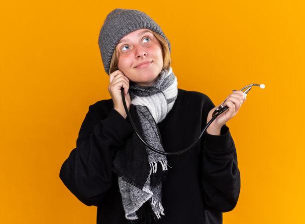 不健康的年轻女子戴着暖和的帽子 脖子上围着围巾 患了感冒和流感 感觉好多了 拿着听诊器站在橙色的墙上微笑着看着旁边