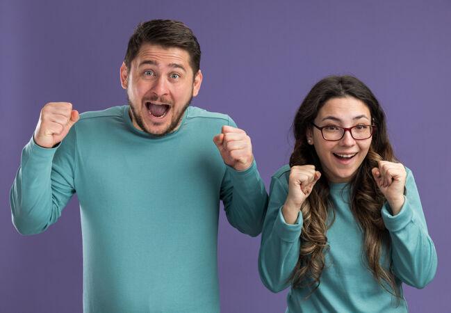 一对穿着蓝色休闲服的年轻漂亮夫妇站在紫色的墙边 男人和女人握紧拳头疯狂地高兴和兴奋
