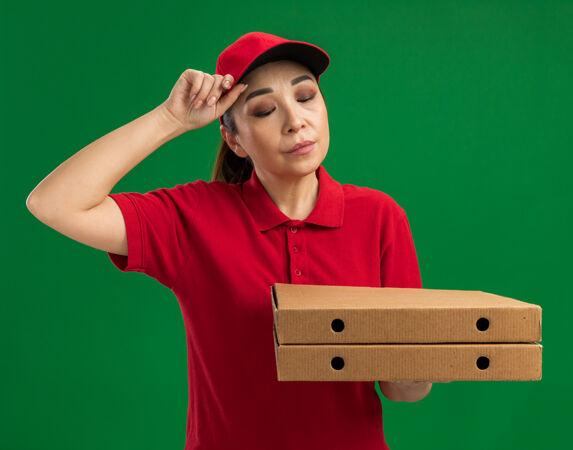 身穿红色制服 头戴鸭舌帽 拿着披萨盒的年轻送货员站在绿色的墙上 神情悲伤地低头看着