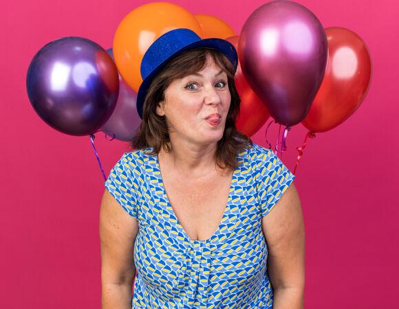 滑稽开朗的中年妇女 戴着派对帽 手持五颜六色的气球 伸出舌头 站在粉色的墙上庆祝生日派对