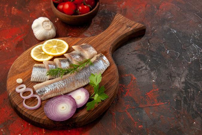 正面图:新鲜的鱼片 洋葱圈和西红柿 深色小吃 肉色海鲜