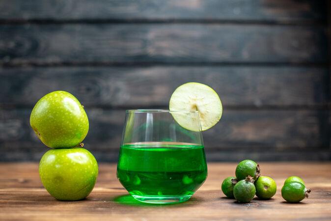 正面图绿色菲约亚果汁内杯绿色苹果木桌酒吧水果色饮料照片鸡尾酒