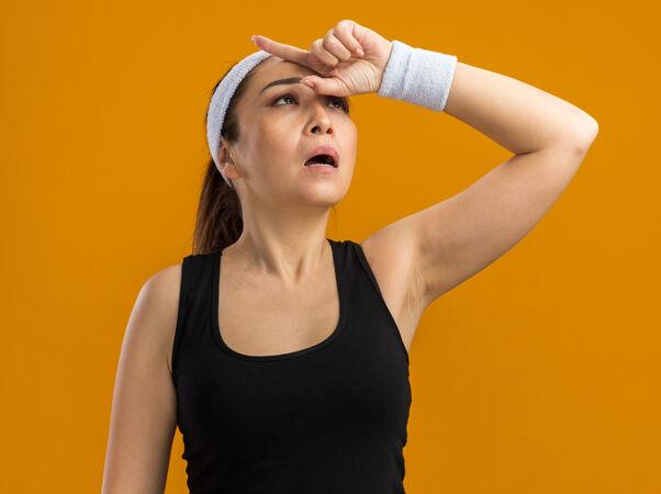 戴着头巾和臂章的年轻健身女士抬起头来 手放在头上 站在橘色的墙上 疲惫不堪 劳累过度