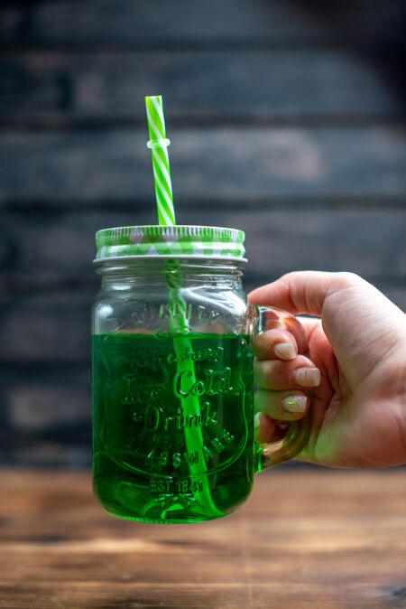 正面图绿色苹果汁内罐 木质桌上有吸管饮料照片鸡尾酒吧水果色