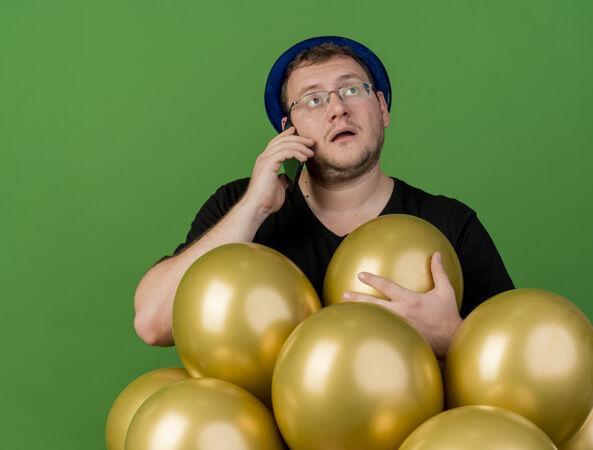 令人印象深刻的成年斯拉夫人戴着眼镜戴着蓝色派对帽拿着氦气球打电话