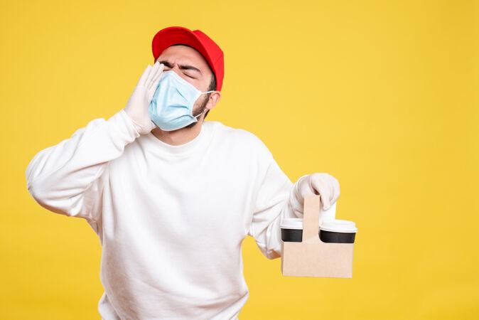 戴着口罩的男信使拿着送咖啡的电话叫黄色的人