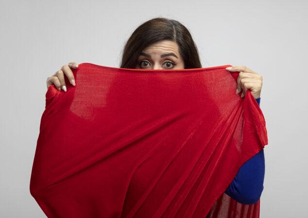 震惊的高加索超级英雄女孩拿着相机看着红色斗篷