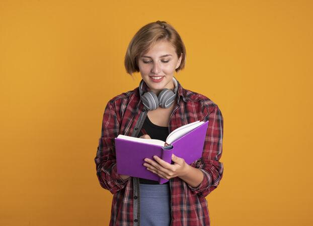 微笑的年轻斯拉夫女学生戴着耳机 背着书包 用笔在书上写字