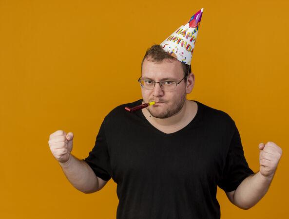 自信的成年斯拉夫人戴着眼镜 戴着生日帽 挥舞着拳头 吹着派对口哨
