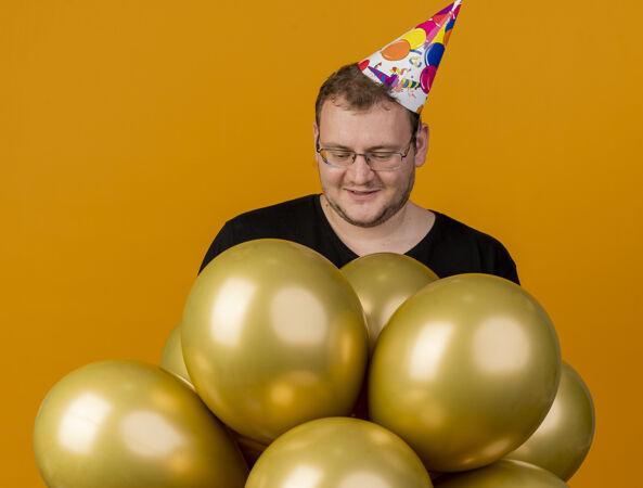 高兴的成年斯拉夫人戴着眼镜戴着生日帽站着氦气球