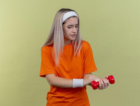 疼痛的年轻白人运动女孩戴着背带 戴着头带和腕带 手持哑铃 看着手