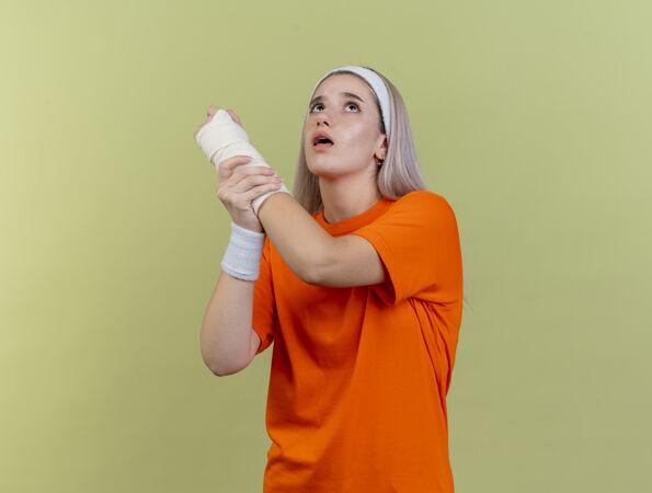 焦虑的年轻白人运动女孩戴着背带 戴着头带和腕带 手拉着手向上看