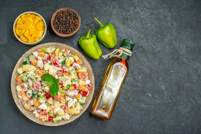 一碗蔬菜沙拉的俯视图 灰色背景上有一碗蔬菜和胡椒油瓶以及甜椒