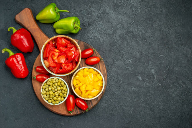 盘子架上蔬菜碗的俯视图 蔬菜在侧面 深灰色背景上为您的文本留出空间