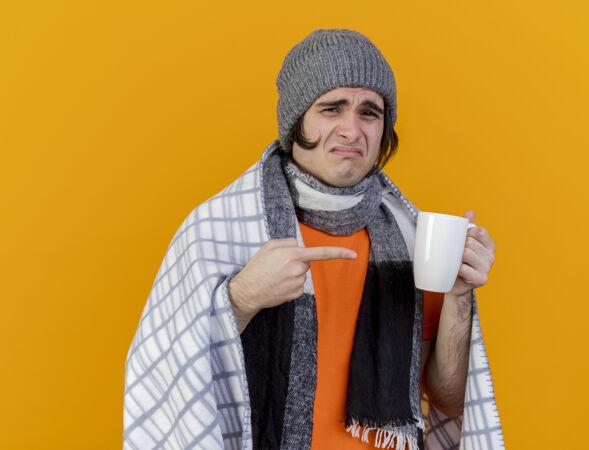 一个戴着冬天帽子 围巾裹着格子布的年轻病患 指着一杯孤立在橙色背景上的茶