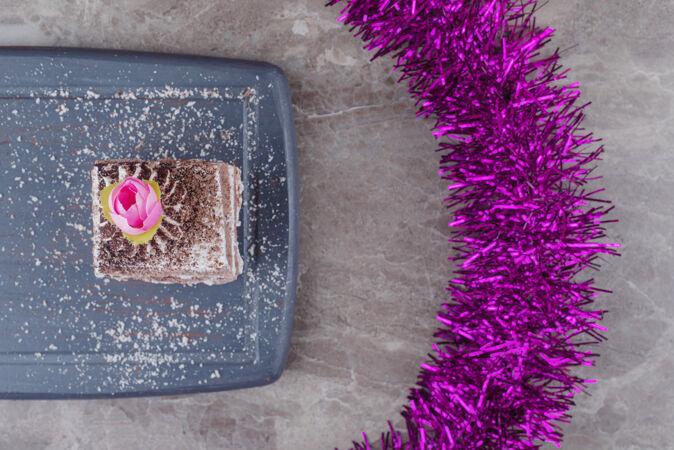 在大理石花环旁边的一块小蛋糕