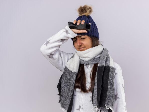 遗憾的是 年轻的病女孩闭着眼睛 戴着冬天的帽子 戴着围巾 拿着电话 把胳膊放在额头上 隔离在白色的背景上