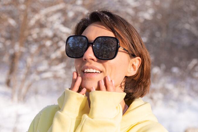 阳光明媚的日子里 雪景冬林中一位年轻美女的画像 身着黄色大套头衫 戴着墨镜 享受着阳光和雪
