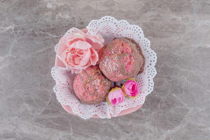 小蛋糕和花冠放在一个铺着桌布的碗里 放在大理石上