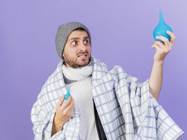 关心的年轻病人戴着冬天的帽子 戴着围巾 看着紫色背景上孤立的灌肠