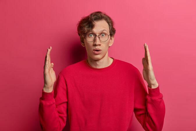 惊呆了的年轻人塑造了巨大的物体 做出了巨大的东西 惊讶地喘息 有惊讶的表情 测量和解释大小 穿着随意 对着粉色的墙壁摆姿势