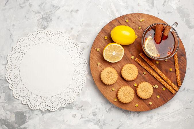 顶视图一杯茶 在浅白色的空间里放着饼干和柠檬