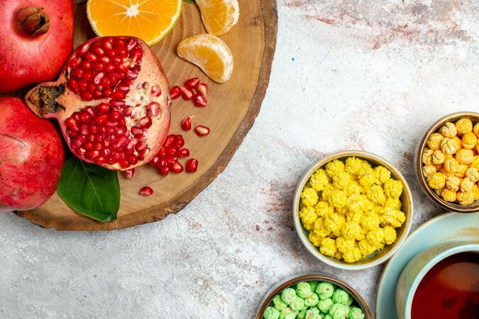 顶视图一杯茶与糖糖果和水果的白色空间