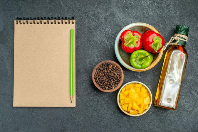 顶视图的甜椒碗在右侧与草药和蔬菜碗油瓶和记事本在一边的绿色桌子上