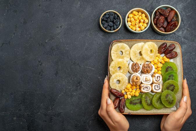 顶视图切片干果菠萝戒指和猕猴桃在灰色的桌子上干果葡萄干甜维生素酸健康