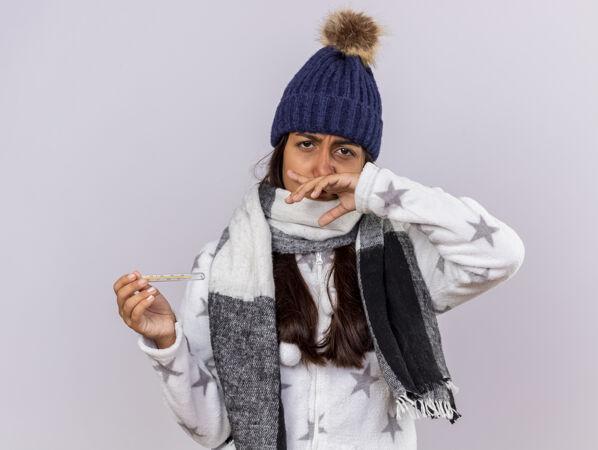 悲伤的生病的年轻女孩戴着冬天的帽子 戴着围巾 拿着温度计 用手擦鼻子 背景是白色的