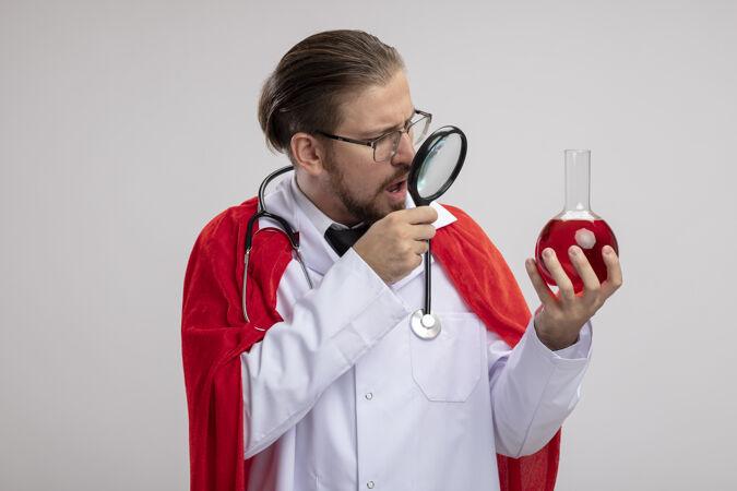年轻的超级英雄穿着医用长袍 戴着听诊器和眼镜 拿着化学玻璃瓶 里面装满了红色液体 放大镜隔离在白色背景上