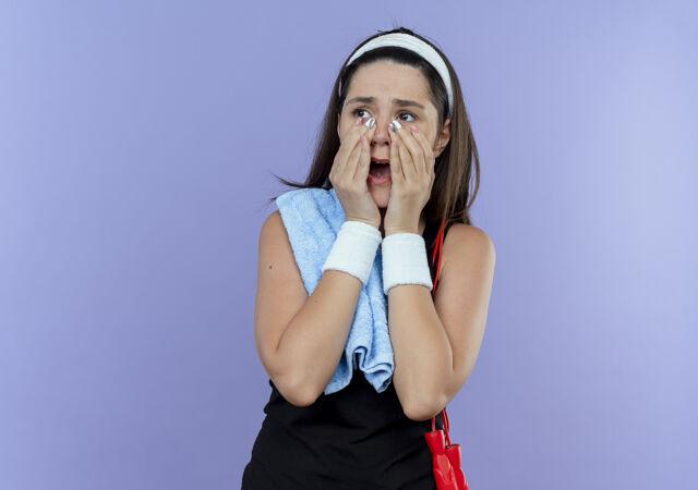 戴着头巾 肩上扛着毛巾 站在蓝色背景下 张大嘴巴的年轻健身女士惊呆了