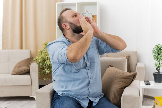 快乐的成年斯拉夫人坐在扶手椅上 手贴着嘴 看着一边假装在客厅里给别人打电话