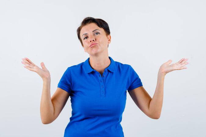 身着蓝色t恤的成熟女性展示无助姿态的肖像 以及犹豫不决的前视图