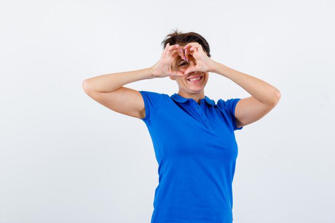 身着蓝色t恤的成熟女性 展现心形 看起来很快乐 正面视图