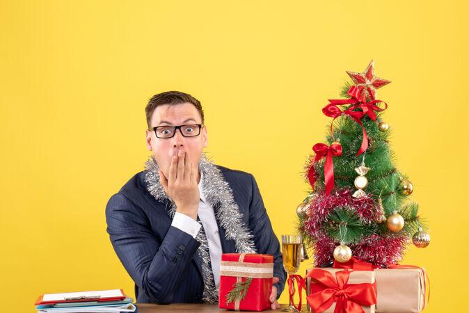 前视图惊奇的男人把手放在嘴边 坐在圣诞树旁的桌子上 呈现黄色背景