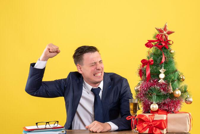 前视图愤怒的男人举起他的手坐在圣诞树和黄色背景上的礼物旁边的桌子上