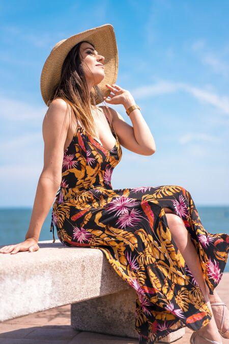 在西班牙拍摄的一个女性穿着花太阳裙 戴着帽子坐在海边的垂直镜头