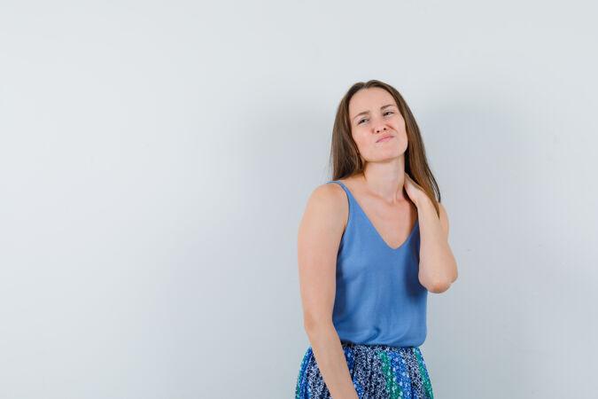年轻女士患有颈部疼痛 在单身 裙子和看起来恼火 前视图