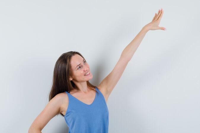 年轻的女士伸开手臂在单打 裙子和看起来开朗 前视图