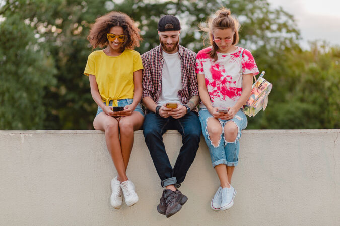 快乐的年轻朋友坐在公园里用智能手机微笑公司
