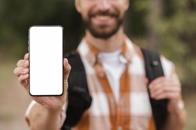 野营时笑脸男手持智能手机的正面图