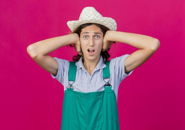 年轻的园丁 穿着连体衣 戴着帽子 用手捂住耳朵