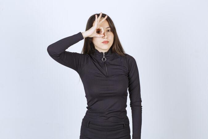 穿黑色衣服的女孩展示着圆形的享受标志