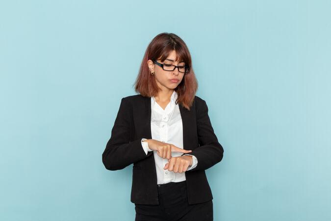 正面图:穿着西装的女上班族在蓝色的表面上指着自己的手腕